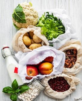 Frisches obst und gemüse in öko-baumwolltaschen auf dem tisch in der küche. milch, kartoffeln, aprikosen, rucola, bohnen vom markt. null-abfall-shopping-konzept.