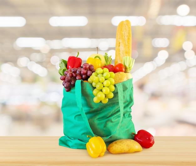 Frisches obst und gemüse in wiederverwendbarer grüner einkaufstasche auf holztischplatte mit supermarktlebensmittelgeschäft verschwommen