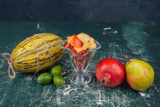 Frisches obst und glas geschnittener obstsalat auf marmoroberfläche.