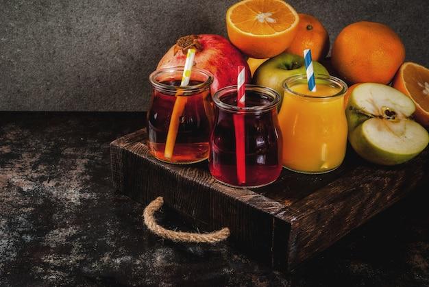 Frisches obst und säfte vielzahl orangen granatapfel und äpfel dunkler rostiger hintergrund mit hölzernem tellersegment