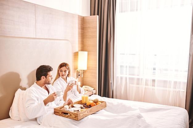 Frisches obstfrühstückspaar isst im hotelzimmerbett?