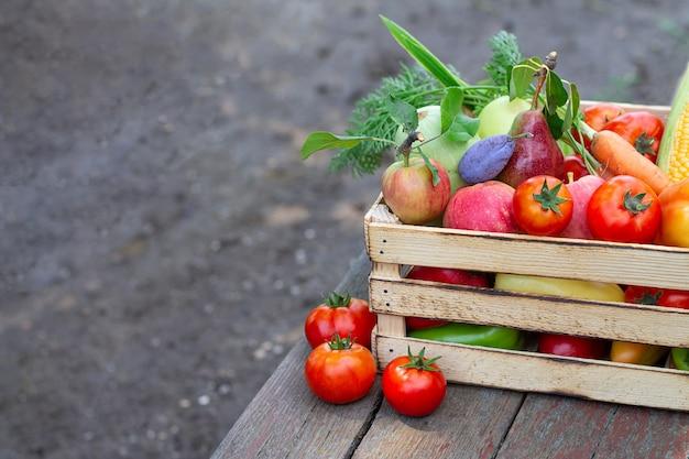 Frisches öko-gemüse und obst auf holzkiste oder kiste auf rustikalem tisch in einem garten. platz für text