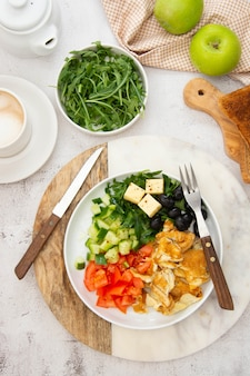 Frisches omelett zum frühstück mit gemischtem gemüse, toastbrerad und einer tasse kaffee. draufsicht.