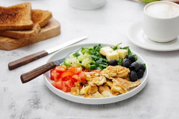 Frisches omelett zum frühstück mit gemischtem gemüse, toastbrerad und einer tasse kaffee.