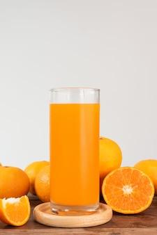 Frisches orangensaftglas und -früchte auf hölzerner tabelle