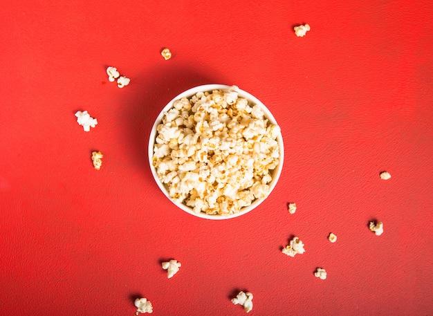 Frisches popcorn aus der schüssel auf rot verschüttet