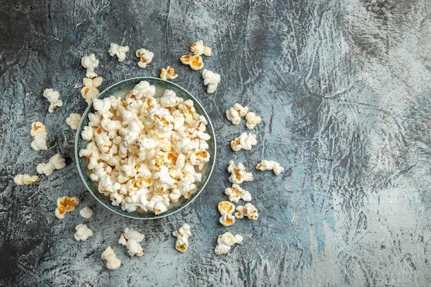 Frisches popcorn der draufsicht auf leichtem schreibtisch