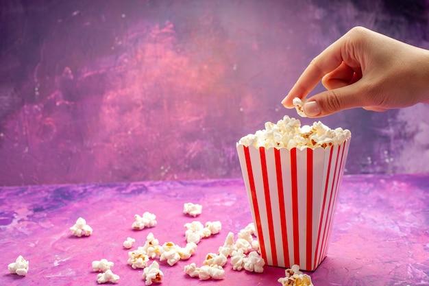 Frisches popcorn der vorderansicht auf hellrosa tischfarbkino-film
