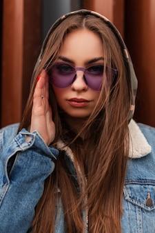 Frisches porträt coole junge frau des hipsters in der glamourösen violetten brille in der übergroßen jeansjacke der modejugend in der nähe der modernen metallischen roten wand. europäisches mädchen glättet trendige tarnhaube in der stadt.
