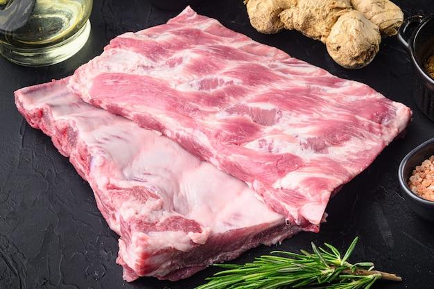 Frisches rack mit rohen schweinerippchen, gewürzt mit gewürzen, auf schwarzem steintisch