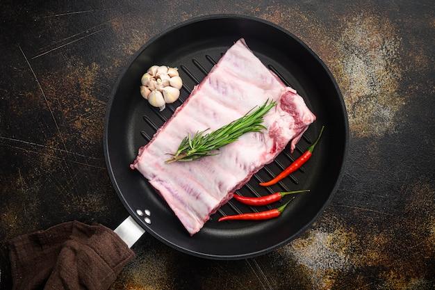 Frisches rack mit rohen schweinerippchen, gewürzt mit gewürzen, in gusseiserner pfanne, draufsicht flach legen