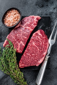 Frisches rohes denver-steak marmor-rindfleisch mit kräutern. schwarzer hintergrund. draufsicht.