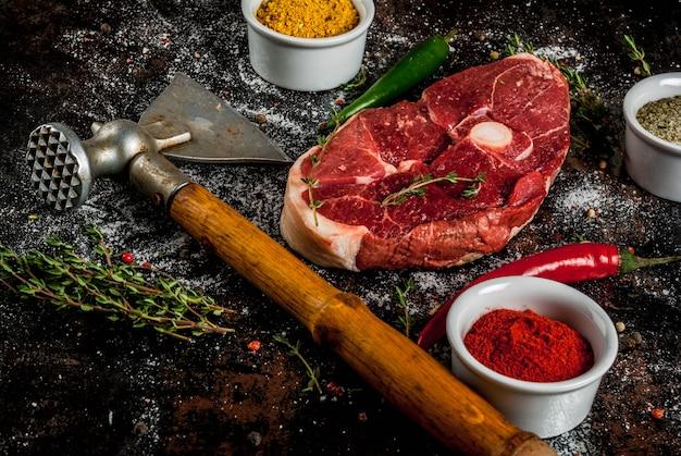 Frisches rohes fleisch. ein stück lammfilet, mit einem knochen, mit einer axt, mit gewürzen zum kochen auf einem alten rostigen schwarzen metalltisch