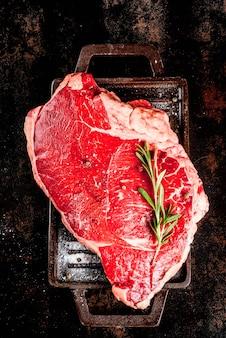 Frisches rohes fleisch, lammfleischmarmorsteak auf einem grillpfannenbrett, mit bestandteilen für das kochen. auf dunkler rostiger metalltabelle copyspace draufsicht