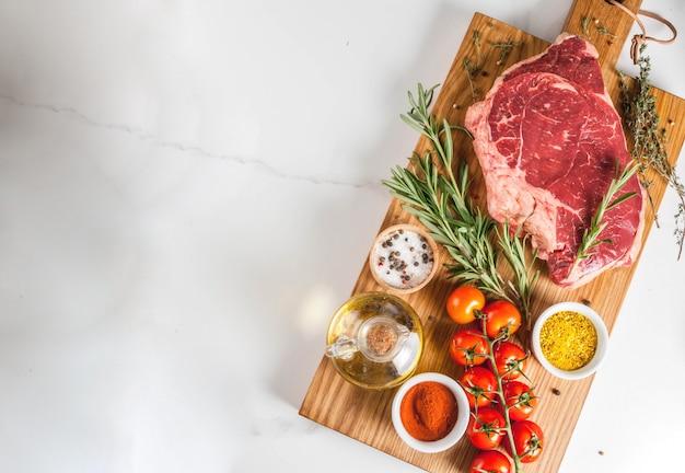 Frisches rohes fleisch, lammfleischmarmorsteak auf einem schneidebrett, mit bestandteilen für das kochen. auf weißer marmortabelle copyspace draufsicht