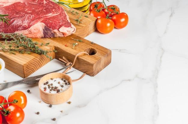 Frisches rohes fleisch, lammfleischmarmorsteak auf einem schneidebrett, mit bestandteilen für das kochen. auf weißer marmortabelle copyspace