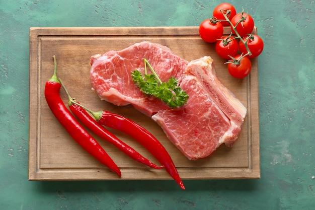 Frisches rohes fleisch mit gemüse auf holzbrett