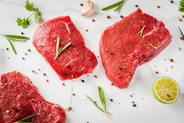 Frisches rohes fleisch. rinderfilet, steaks, auf einem weißen marmortisch. mit olivenöl, gewürzen zum kochen - basilikum, rosmarin, koriander, petersilie, knoblauch, zitrone, salz, pfeffer. draufsichtkopienraum