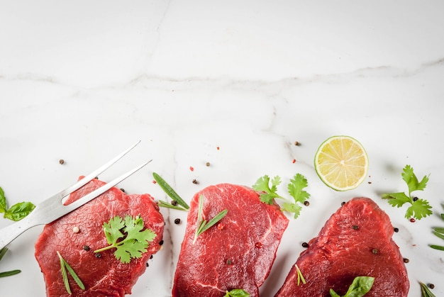 Frisches rohes fleisch. rinderfilet, steaks, auf einem weißen marmortisch. mit olivenöl, gewürzen zum kochen - basilikum, rosmarin, koriander, petersilie, knoblauch, zitrone, salz, pfeffer. kopieren sie die draufsicht des raumes