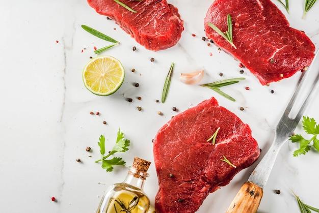 Frisches rohes fleisch. rinderfilet, steaks, auf einem weißen marmortisch. mit olivenöl, gewürzen zum kochen von basilikum, rosmarin, koriander, petersilie, knoblauch, zitrone, salz, pfeffer. ansicht von oben