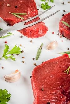 Frisches rohes fleisch rinderfiletsteaks auf einem weißen marmortisch mit olivenölgewürzen zum kochen - basilikum rosmarin koriander petersilie knoblauch zitronensalz pfeffer