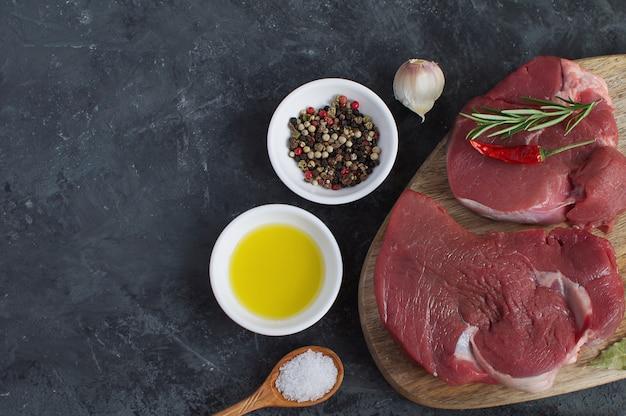 Frisches rohes fleisch rindersteak olivenöl gewürze heißsalz holzlöffel chili pepper knoblauch rosmarin