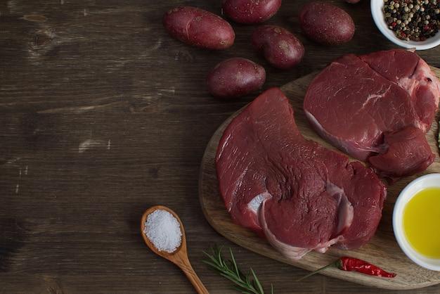 Frisches rohes fleisch rindfleisch steak olivenöl gewürze heißes salz holzlöffel pfeffer rosmarin