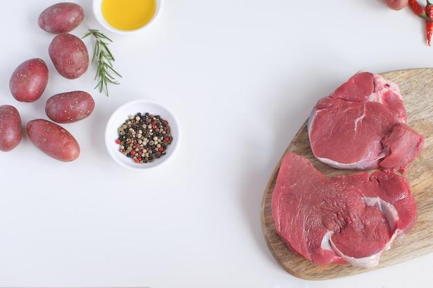 Frisches rohes fleisch rindfleisch steak olivenöl gewürze pfeffer rosmarin rohe kartoffel