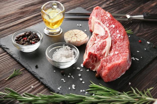 Frisches rohes fleisch und gewürze auf schieferplatte