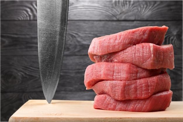 Frisches rohes fleisch und messer auf hintergrund