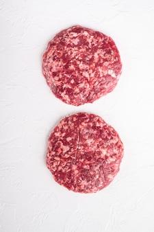 Frisches rohes, gehacktes hausgemachtes bauern-rindfleisch-burger-kotelett auf weißem stein on