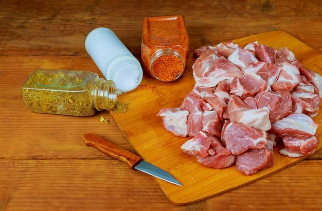 Frisches rohes gehacktes rindfleisch auf einem hölzernen schneidebrett mit gewürzen, kräutern und gemüse.