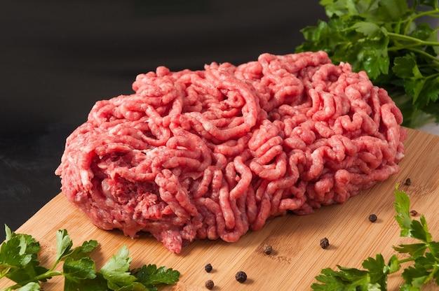 Frisches rohes gehacktes schweinefleisch und rindfleisch auf einem holzbrett