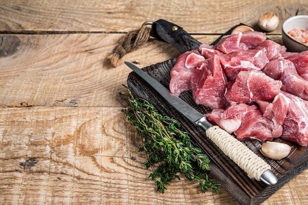 Frisches, rohes, gewürfeltes schweinefleisch mit gewürzen auf einem hölzernen metzgerbrett