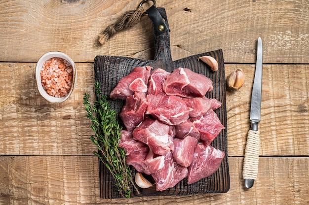 Frisches rohes gewürfeltes schweinefleischjungenfleisch mit gewürzen auf einem hölzernen metzgerbrett. holztisch. draufsicht.