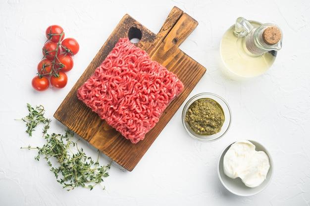 Frisches rohes hackfleisch für fleischbällchen mit gewürzen pfeffer, salz, mozzarella, pesto-set, auf weißem steintisch, draufsicht flach legen