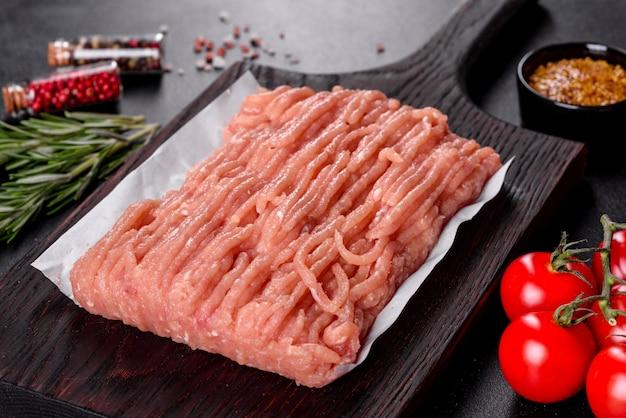 Frisches rohes hühnerhackfleisch auf einem dunklen hölzernen schneidebrett
