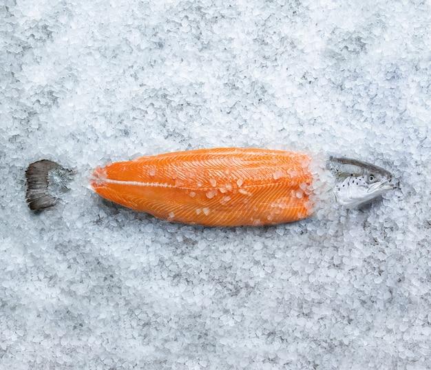 Frisches rohes lachsfischsteak auf eis über grauem steinhintergrund