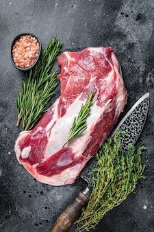 Frisches rohes lamm- oder ziegenschulterfleisch mit metzgermesser. schwarzer hintergrund. ansicht von oben.