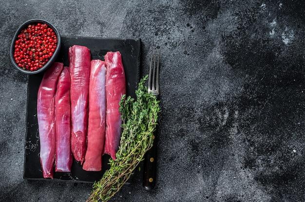 Frisches rohes lammfiletfilet, hammelfleischfleisch auf marmorbrett mit thymian. draufsicht.