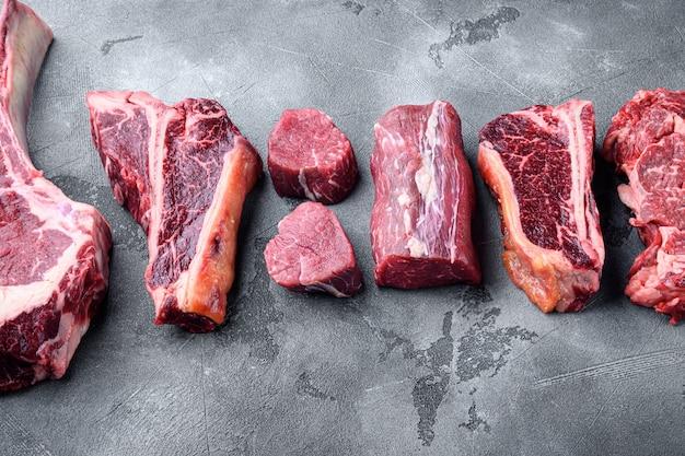Frisches rohes prime black angus beef marmoriert und trocken gereift steaks, tomahawk, t-bone, club steak, rib eye und filetschnitte, auf grauem steinhintergrund, mit kopierraum für text