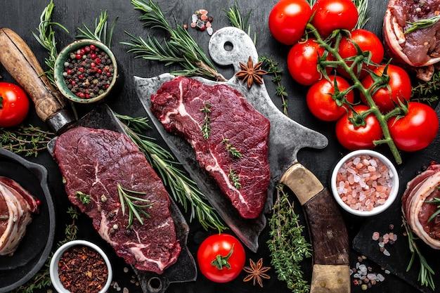 Frisches rohes prime black angus rinder-rumpsteak oder top-lenden-rindfleisch-steak serviert auf altem fleischer auf schwarzem hintergrund. ansicht von oben.