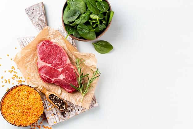 Frisches rohes ribeye-steak auf holzschneidebrett mit spinatlinsen und rosmary
