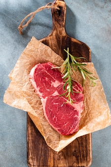 Frisches rohes ribeye-steak auf holzschneidebrett