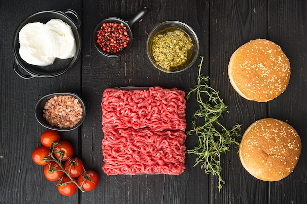 Frisches rohes rinderhackfleisch für frikadellenburger mit sesambrötchen auf schwarzem holztisch