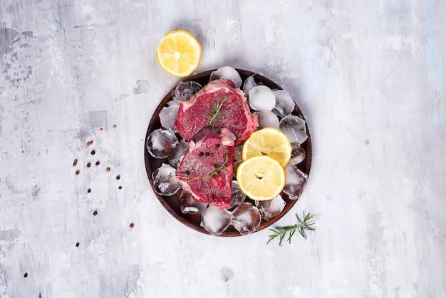 Frisches rohes rindfleisch auf einer hölzernen platte mit zitronenscheibe und eis. schlanke proteine.