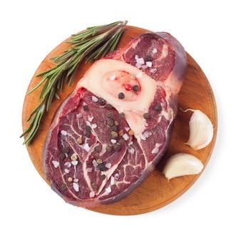 Frisches rohes rindfleischsteak mit knochen und rosmarin auf schneidebrett lokalisiert auf weißem hintergrund. draufsicht, flach liegen.