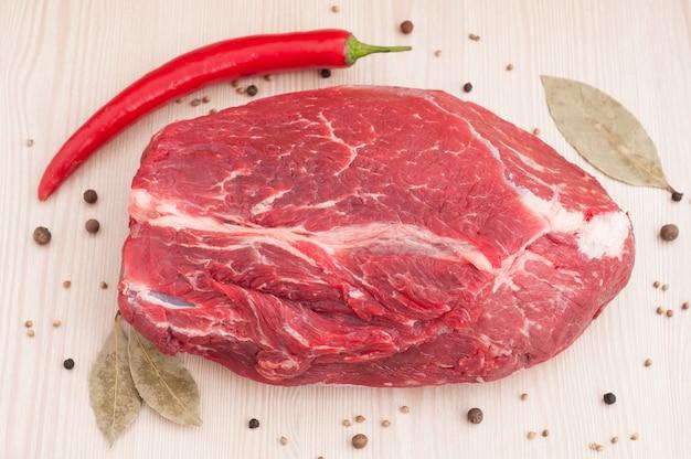 Frisches rohes rotes rindfleischfleisch mit gewürzen auf holztisch