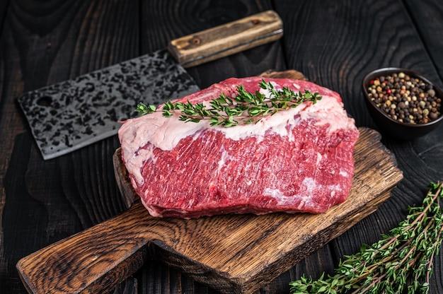 Frisches rohes rundes roastbeef-fleisch auf einem metzger-schneidebrett mit hackmesser geschnitten. schwarzer hölzerner hintergrund. ansicht von oben.