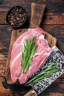 Frisches rohes schweineschulterfleisch geschnitten mit zutaten und gewürzen auf küchentisch. dunkler holztisch. draufsicht.